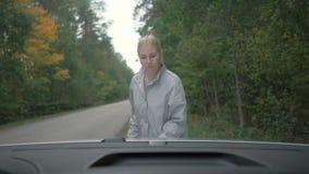 La muchacha abre la capilla de un coche el coche de las muchachas analiza en el camino Visión por dentro del coche metrajes