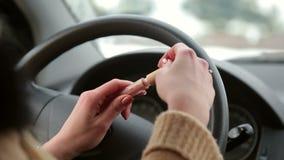 La muchacha abre el lápiz labial que se sienta detrás de la rueda de un coche almacen de video