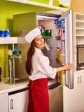 La muchacha abre el refrigerador Fotos de archivo libres de regalías