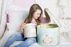 La muchacha abre el regalo Foto de archivo libre de regalías