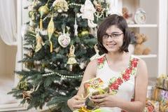 La muchacha abre el regalo de la Navidad Fotografía de archivo