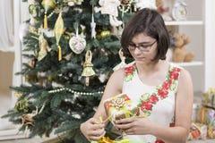 La muchacha abre el regalo de la Navidad Imagen de archivo libre de regalías