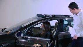 La muchacha abre el techo corredizo del coche eléctrico almacen de video