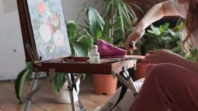 La muchacha abre el tubo, exprime la pintura sobre la paleta Paleta del artista con la pintura y los cepillos de aceite almacen de metraje de vídeo