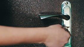 La muchacha abre la cerradura de puerta con una llave grande del hierro almacen de video