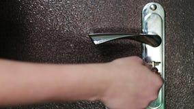 La muchacha abre la cerradura de puerta con una llave grande del hierro metrajes