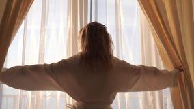 La muchacha abre las cortinas almacen de video