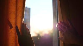 La muchacha abre las cortinas en la madrugada Los rayos del sol pasan a través de la ventana y de los fingeres almacen de metraje de vídeo