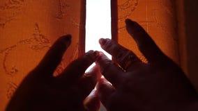 La muchacha abre las cortinas en la madrugada Los rayos del sol pasan a través de la ventana y de los fingeres almacen de video