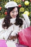 La muchacha abre los panieres con el árbol de navidad Imagen de archivo