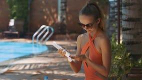 La muchacha abre la protección solar para manchar el cuerpo en Sunny Day