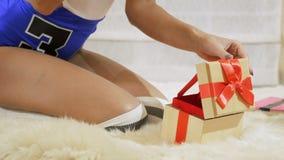 La muchacha abre un rectángulo de regalo almacen de video