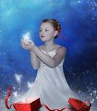 La muchacha abre un rectángulo con el regalo Fotos de archivo