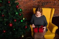 La muchacha abre un regalo de la Navidad Foto de archivo libre de regalías