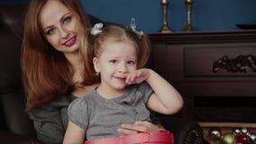 La muchacha abre un regalo del Año Nuevo con su madre, la Navidad 2019 almacen de video