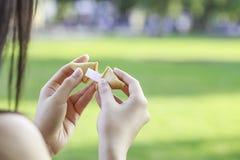 La muchacha abre una galleta de la suerte Imagen de archivo libre de regalías