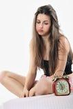 La muchacha aburrida mira soplar del despertador Fotos de archivo libres de regalías