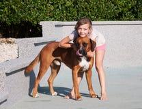 La muchacha acaricia su perro Foto de archivo
