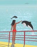 La muchacha acoge con satisfacción delfínes Imagen de archivo libre de regalías