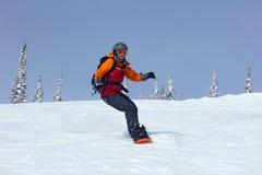 La muchacha acomete abajo de la cuesta en una snowboard Fotografía de archivo libre de regalías
