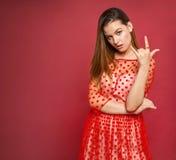 La muchacha activa en un vestido rojo muestra los cuernos Imagenes de archivo