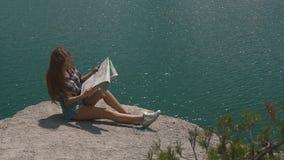 La muchacha activa joven del backpacker descansa sobre roca de la montaña sobre la superficie grande del agua del lago y de la mi almacen de video