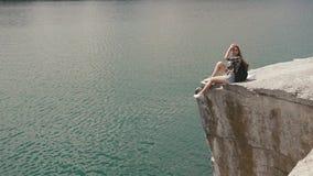 La muchacha activa joven del backpacker se relaja descansando sobre roca de la montaña sobre la superficie grande del agua del la almacen de video