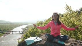La muchacha activa joven se relaja practicando yoga en la roca de la montaña River Valley ancho como fondo almacen de video