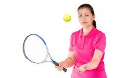 La muchacha activa lanzó la bola para arriba para el tenis en un blanco Imagenes de archivo