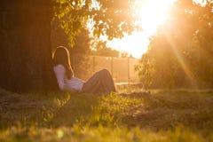 La muchacha admira la puesta del sol Foto de archivo