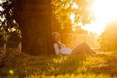 La muchacha admira la puesta del sol Fotos de archivo libres de regalías