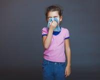 La muchacha adolescente 5 años de aspecto europeo estornuda Foto de archivo