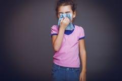 La muchacha adolescente 5 años de aspecto europeo estornuda Fotos de archivo