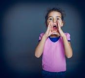 La muchacha adolescente abrió su boca está invitando a un gris Fotos de archivo libres de regalías