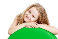 La muchacha adolescente adorable puso sus manos en una bola grande Imagenes de archivo