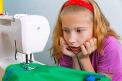 La muchacha adolescente asustó por su error al coser Fotografía de archivo libre de regalías