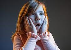 La muchacha adolescente atractiva joven que parece sorprendida aislado en azul marino Fotos de archivo
