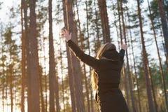 La muchacha adolescente aumentó las manos de detrás en bosque del pino del invierno en puesta del sol Foto de archivo libre de regalías