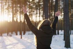 La muchacha adolescente aumentó las manos de detrás en bosque del pino del invierno en puesta del sol Imágenes de archivo libres de regalías