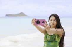 La muchacha adolescente Biracial arma la mentira en la playa que se relaja por el agua del océano Fotos de archivo libres de regalías