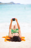 La muchacha adolescente Biracial arma la mentira en la playa que se relaja por el agua del océano Fotografía de archivo