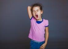La muchacha adolescente bosteza soñoliento abierto su boca en gris Fotografía de archivo libre de regalías
