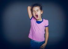 La muchacha adolescente bosteza soñoliento abierto su boca en un gris Imagenes de archivo