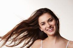 La muchacha adolescente cabelluda, última oscura, pelo que sopla, sonríe a la cámara Foto de archivo