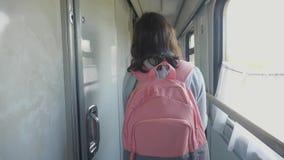 La muchacha adolescente camina en un coche del compartimiento del tren con forma de vida una mochila concepto del ferrocarril del almacen de video