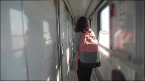 La muchacha adolescente camina en un coche del compartimiento del tren con forma de vida una mochila concepto del ferrocarril del metrajes