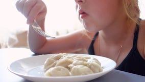 La muchacha adolescente come las bolas de masa hervida con una placa blanca en el fondo de la ventana almacen de metraje de vídeo