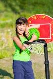 La muchacha adolescente con baloncesto muestra el pulgar para arriba Foto de archivo