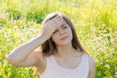 La muchacha adolescente con dolor de cabeza lleva a cabo su mano a su frente Fotos de archivo