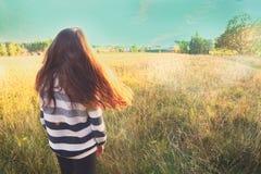 La muchacha adolescente con el pelo flojo marrón largo permanece detrás Foto de archivo
